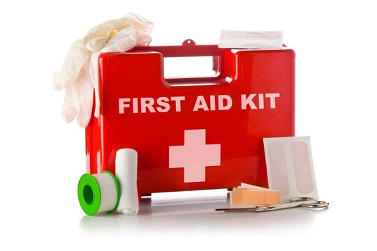 Red first aid medical kit box with scissors, bandage, tape and gloves standing over white