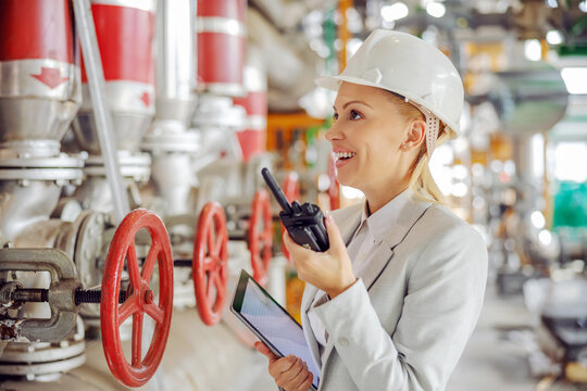 Middle aged experienced hardworking female supervisor with helmet in suit holding tablet in hands and talking on walkie talkie with employee while standing in heating plant.