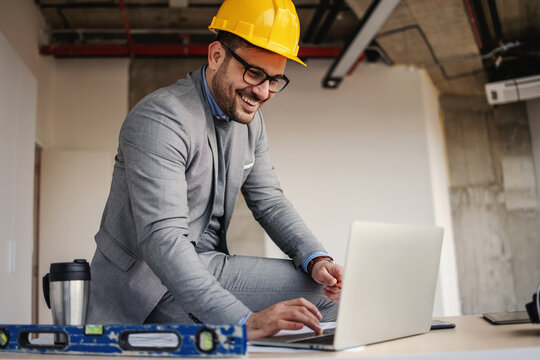 Smiling architect sitting on desk at construction site and using laptop for improving project.