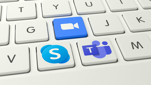 Logos of the competing video conference systems Skype, Zoom and Microsoft Teams (l.t.r.) as keys on a white keyboard.
