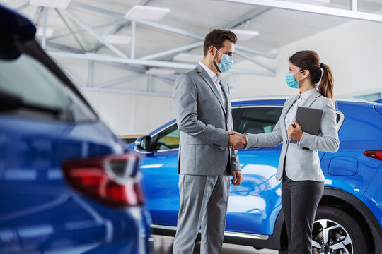Car seller standing in car salon with a client and shaking hands with him. They made and agreement. They both have face masks because it's corona virus outbreak.
