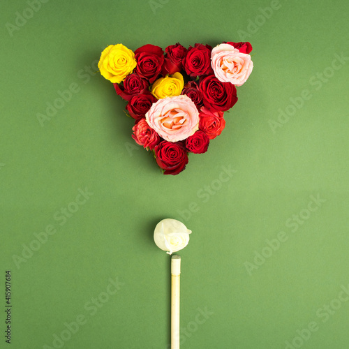 Creative arrangement with colorful flowers on a green background and with a billiard cue. Minimal nature and Mother's day concept. Flat lay.
