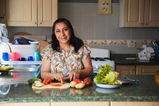 Adult woman cutting fresh vegetables in her kitchen-Hispanic woman preparing healthy salads with fresh vegetables and organic-mama smiling at camera