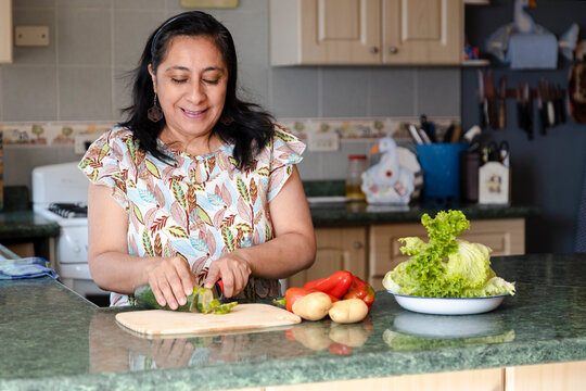 Smiling middle aged hispanic woman making fresh salad in her kitchen - lady in cooking healthy food with organic vegetables