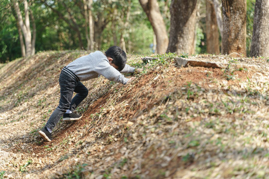 Asian boy playing with steep soil slopes at a public park in Thailand
