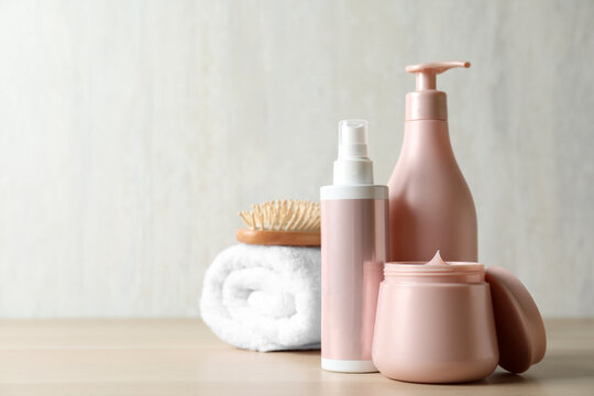 Different hair care products, towel and brush on wooden table. Space for text