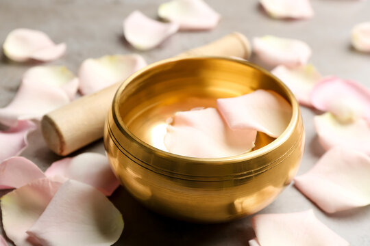 Golden singing bowl with petals on grey table, closeup. Sound healing