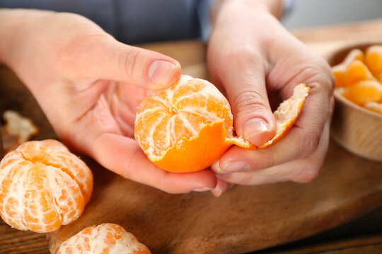 Woman peeling fresh ripe tangerine at wooden table, closeup