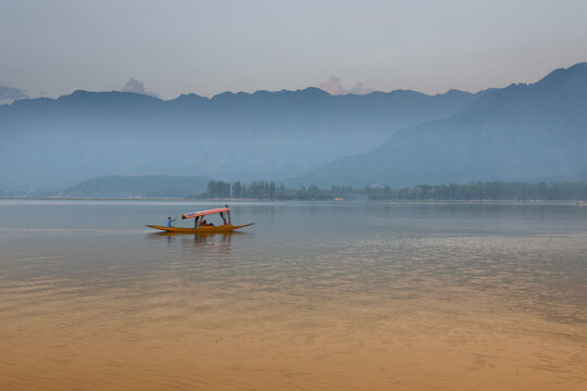 Reflection of Himalayan mountains on Dal Lake, Srinagar, Jammu and Kashmir, India. Houseboats floating on the lake in late afternoon.