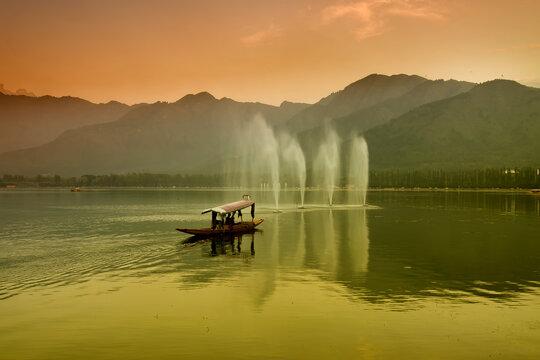Reflection of Himalayan mountains on Dal Lake, Srinagar, Jammu and Kashmir, India. Houseboats floating near fountains on the lake in late afternoon.