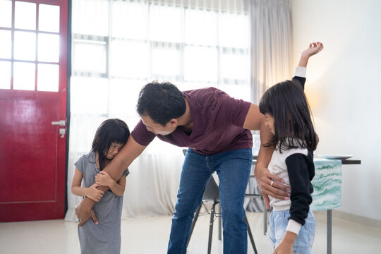 asian little kids, sister fighting over a toy. the conflict between children father try to stop it