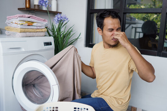 Housework. asian Man doing laundry at home loading clothes into washing machine bad odor. smell badly