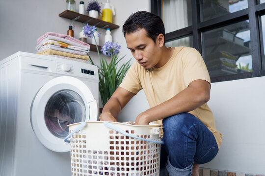 Housework. asian Man doing laundry at home loading clothes into washing machine