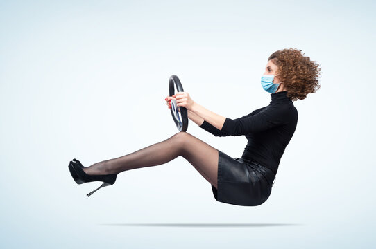 Young woman wearing a respiratory mask from coronavirus drives a car, on light blue background. Pandemic travel concept.