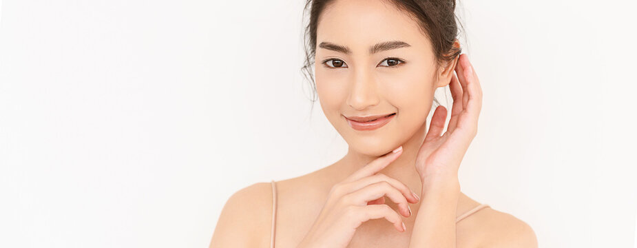 Closeup portrait of beauty asian woman with fair perfect healthy glow skin hand touching chin isolated on white, young beautiful asia girl with pretty smile on face. Beauty korean spa skincare banner