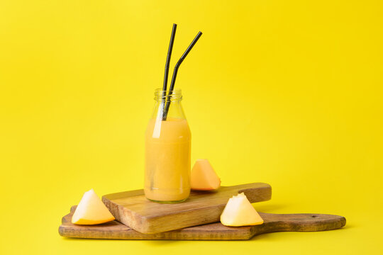 Bottle with melon smoothie on color background