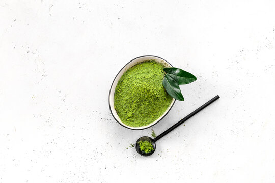 Bowl with powdered matcha tea and scoop on light background