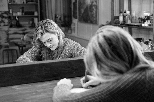 Young woman sits at a table in front of a mirror and writes something with a pen in a notebook. Shallow focus. Black and white.