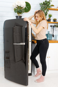 Young attractive woman open a door of a black refrigerator on the domestic kitchen.