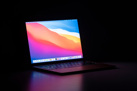 Portland, OR, USA - Feb 22, 2021: The new MacBook Air with Apple's M1 chip and the latest macOS Big Sur isolated on a desk in the dark.