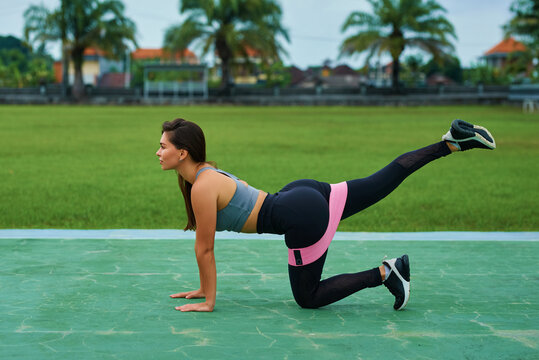 Fitness woman doing exercise with resistance band outdoors. .