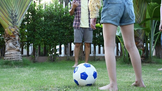 Asian family play soccer in garden at home. Parent with kid and grandfather play football in backyard.