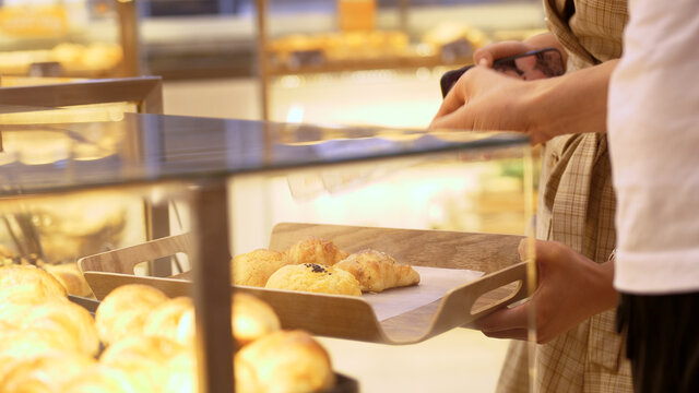 Someone using tongs takes a donut from a shelf in the confectionery department of a bakery or supermarket. 4k