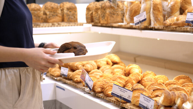 Someone takes a bun in the confectionery department of a bakery or supermarket. 4k