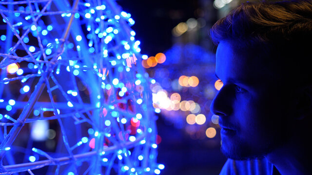Side view of young millennial handsome man standing outside at night with lights and street out of focus in background