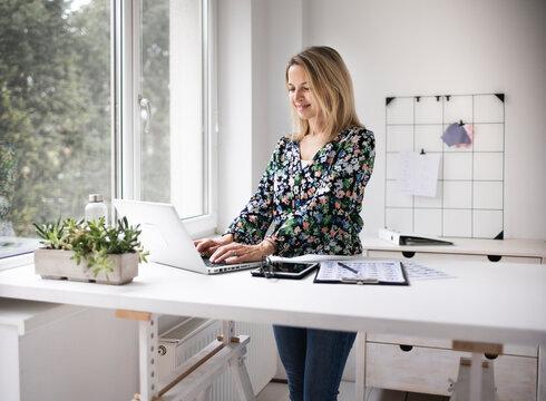 Businesswoman working at ergonomic standing desk.