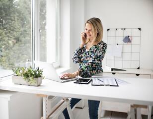 Fototapeta Businesswoman telephoning customer using cellphone while working at ergonomic standing desk in office.