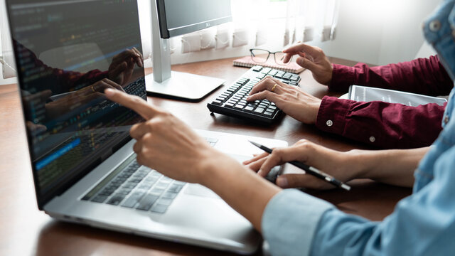 Team of Programmer working to find solution to problem and coding technologies in a software developing company office.