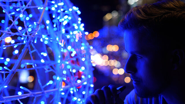 Bokeh view of a stylish young handsome man smoking electronic cigarette and breathing out smoke thru nose in city at night in summer