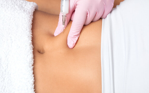 A doctor of aesthetic cosmetology makes lipolytic injections to burn body fat on a woman's stomach and body. Female aesthetic cosmetology in a beauty salon.