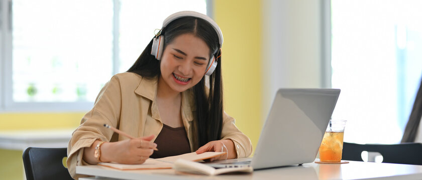 Female student with headphone smiling while doing home working with stationery and laptop