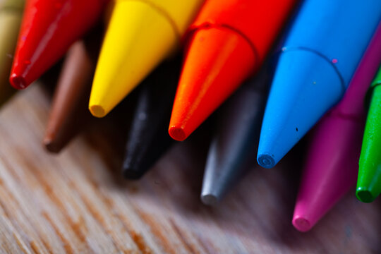 Variety of colored wax pencils on wooden table. Creativity concept..