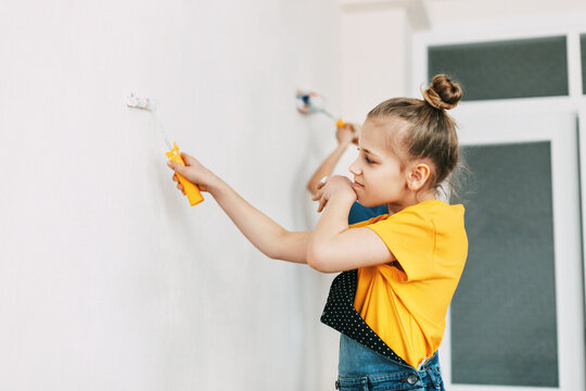 A girl in a denim overalls and a yellow T-shirt helps to paint the walls in an apartment white