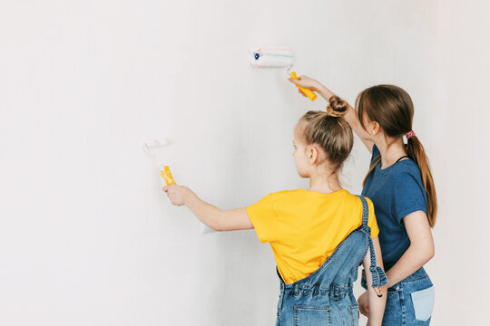 Two sisters are painting the walls of the house white, in denim overalls and a bright yellow T-shirt, home renovation