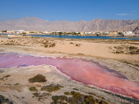 Pink lake in Ras al Khaimah surrounded by seaside, desert sand and mountains in the UAE
