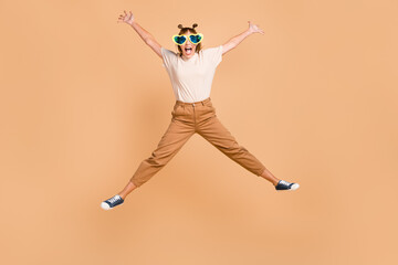 Wall Mural - Full length photo of lady jump star form wear eyeglasses t-shirt trousers footwear isolated beige color background
