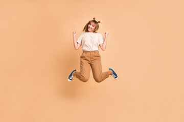 Wall Mural - Full length photo of young excited girl jump up celebrate win victory success fists hands isolated over beige color background