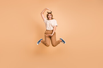 Wall Mural - Full length photo of young lady jump hands frame wear t-shirt pants footwear isolated beige color background