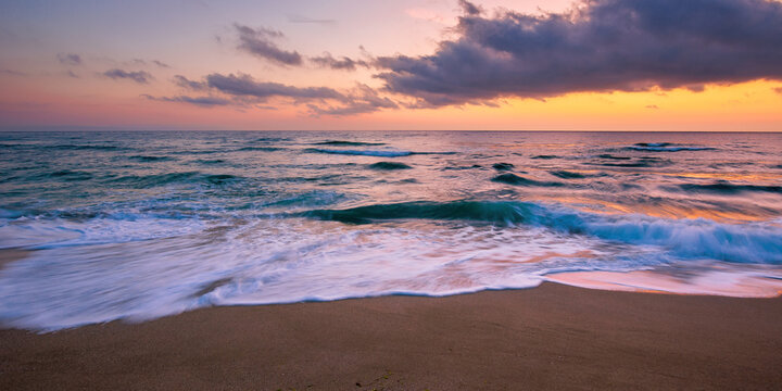 sea beach with dramatic sky at sunrise. beautiful vacation background. waves rolling on the sand in morning light