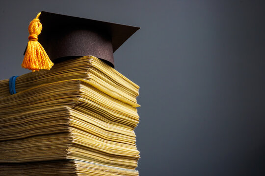 Cost of education concept. Graduation cap and stack of cash for college.