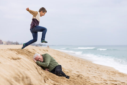 Funny boy jumping over his grandfather on the beach