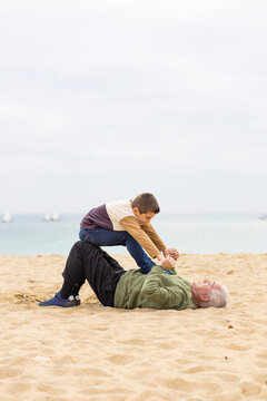 Funny boy and his grandfather playing stretched out in the sand on the beach