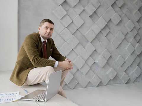 Portrait of a businessman looking into the camera. Laptop and paper. Empty space.