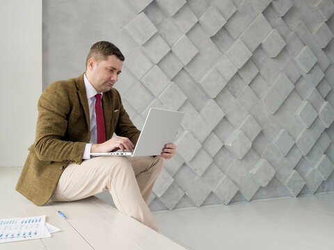 A man works with a laptop and business papers. Empty space.
