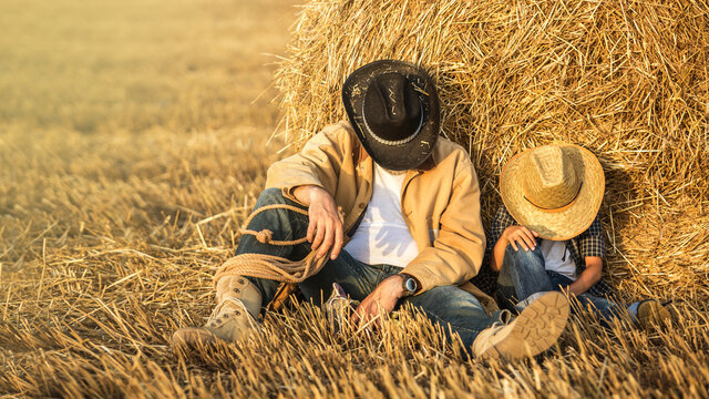 Father and son resting in the field wear hats, shirts and jeans. Son like as father concept