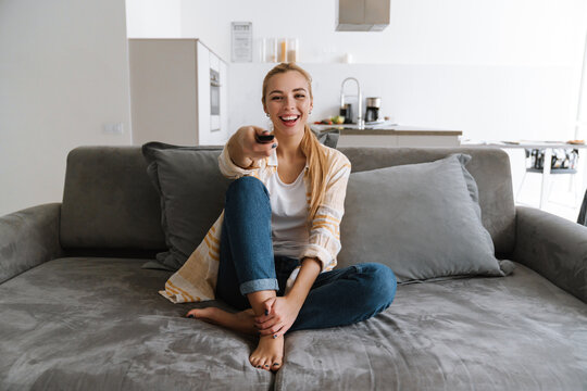 Happy blonde woman watching tv with remote control while sitting on couch